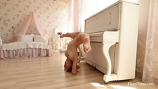 acrobatic hottie nino belover shows her skills near the piano
