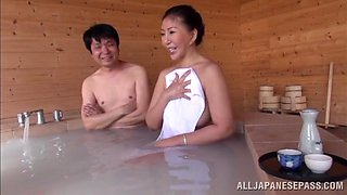 Busty Japanese milf gets fucked by two dudes in a sauna