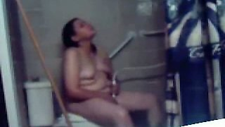 Chubby amateur dark haired nympho masturbates on the toilet bowl