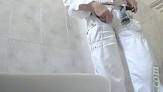 Stranger chick in white pants pisses in the public toilet room
